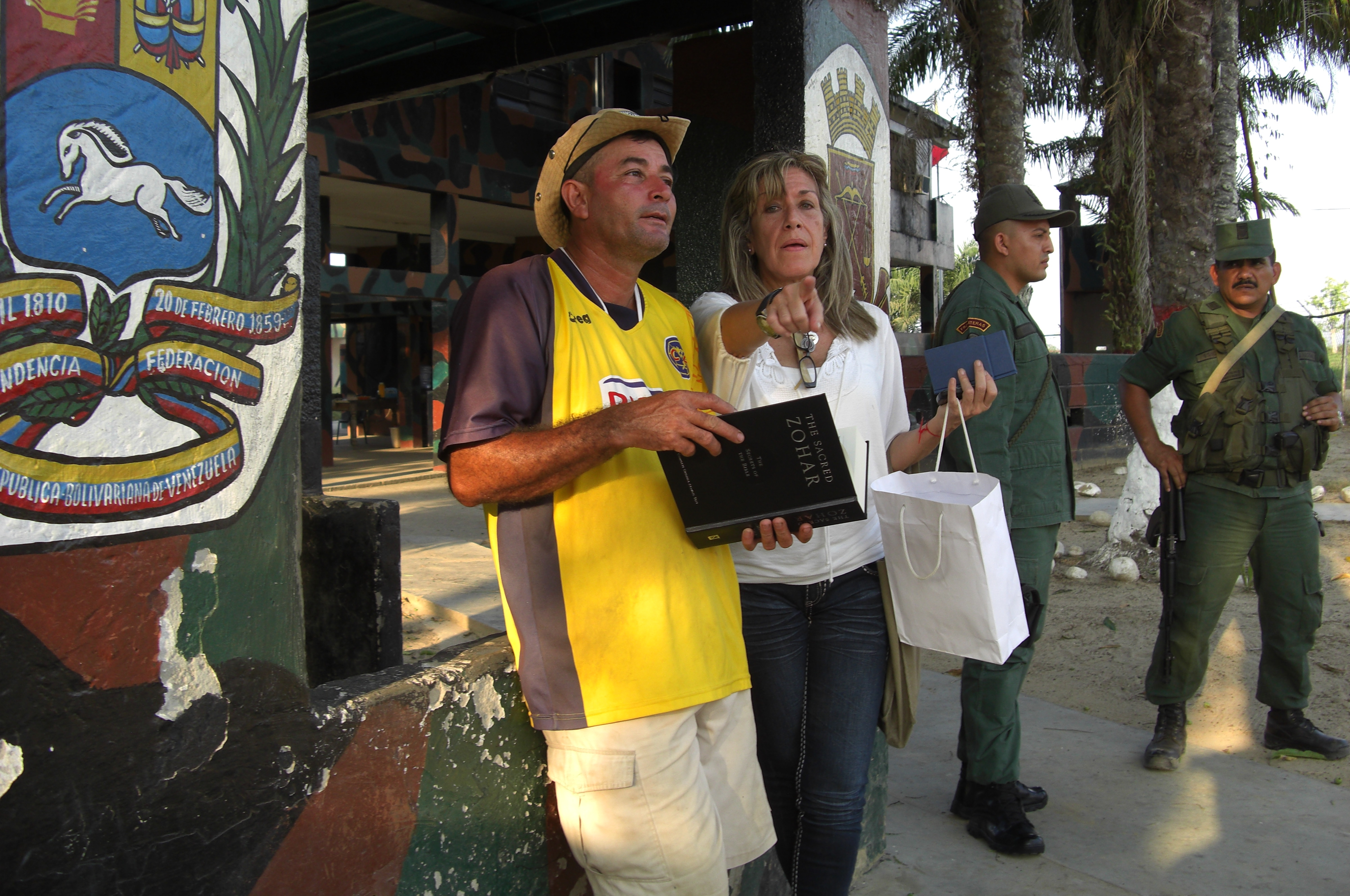 A Kabbalah Centre volunteer shares a Zohar near the Colombia/Venezuela border as policemen look on